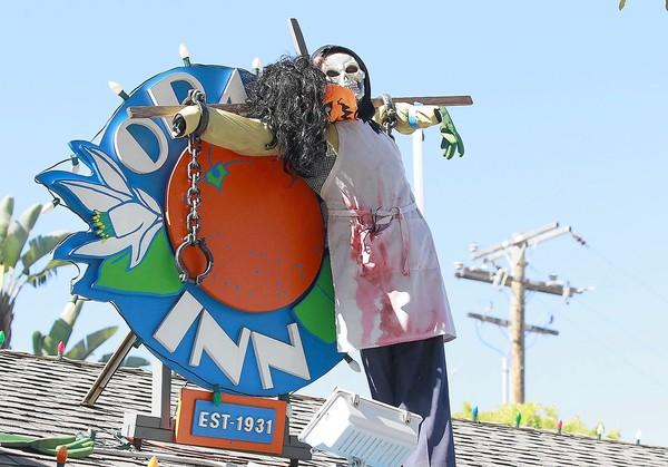 A scarecrow is displayed on the roof sign of the Orange Inn, which is part the Chamber of Commerce's Scarecrow Fest and Contest.
