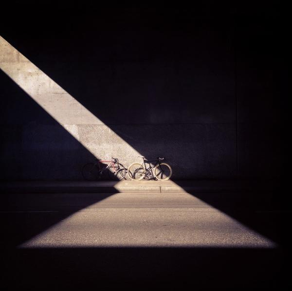 Two bicycles are caught in a stream of sunshine on Pico Boulevard under the 110 Freeway overpass.