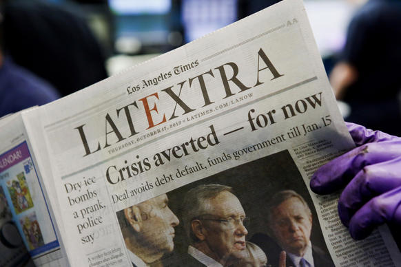 Press operators check the print quality of the Los Angeles Times LATExtra section, whose front page reported news of the government reopening after 16 days and the debt ceiling being raised.