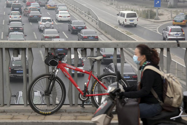A woman wearing a protective mask rides a scooter on a polluted day last week in Beijing.
