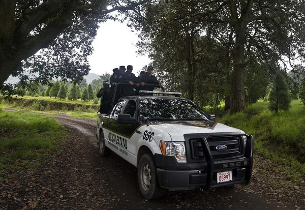 Mexican police officers are seen patrolling rural tracks near a park in the municipality of Tlalmanalco near Mexico City. Mexican authorities acknowledged this week that they will miss another deadline for vetting the nation's federal, state and local police officers.