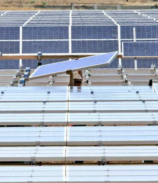 A solar energy panel is carried to be placed in a solar energy field under construction for the Sacramento Municipal Utility District.