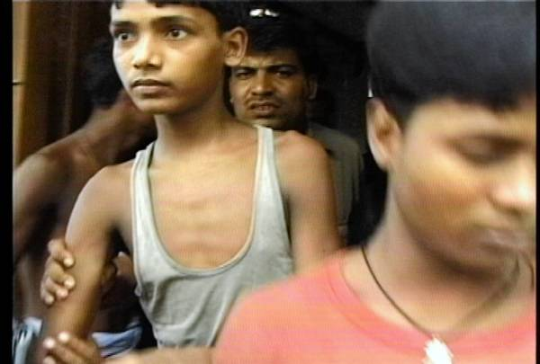 Young workers flee during a raid by police and anti-slavery activists at the carpet looms where they were forced to work in Bihar state, in northeast India, in 2005.