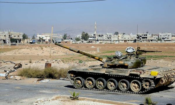 A Syrian army tank carries out a patrol in north Damascus.