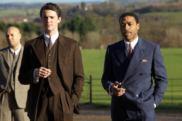 "Matthew Goode (brown suit) and Chiwetel Ejiofor (right) in ""Dancing on the Edge."""