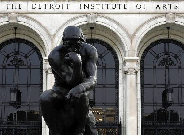 The Thinker, bronze sculpture by Auguste Rodin on a stone pedestal outside the Detroit Institute of Arts Museum.