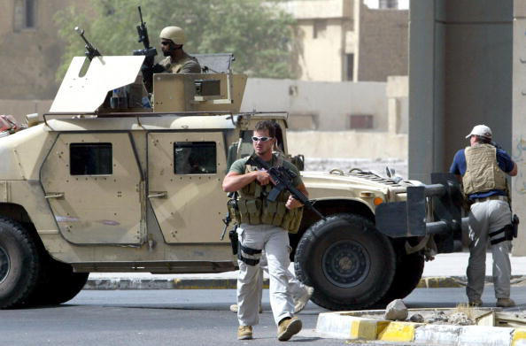 A picture taken on July 5, 2005 shows contractors of the US private security firm Blackwater securing the site of a roadside bomb attack near the Iranian embassy in central Baghdad. Iraq will not renew the operating license of controversial US security firm Blackwater Worldwide, an interior ministry official said on January 29, 2009.