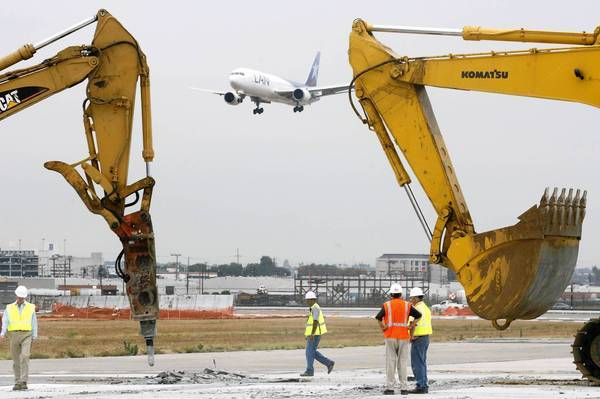 A plane comes in for a landing as AX's southernmost runway is demolished during a relocation project in 2006.A lawsuit has been filed over the quality of the work on the runway.