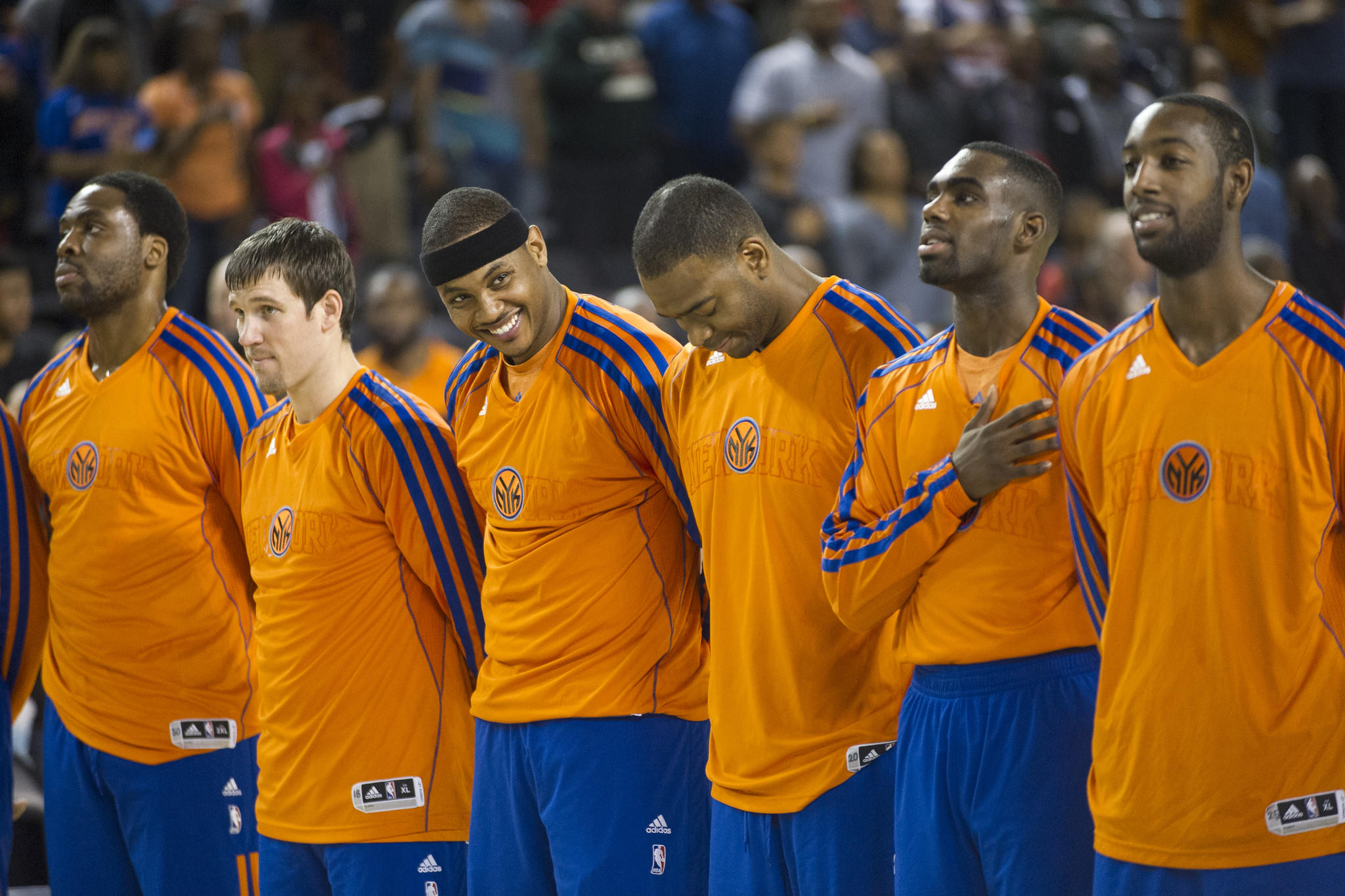 Carmelo Anthony, third from left, lines up with his New York Knicks teammates during the playing of the national anthem before the Baltimore Basketball Classic.