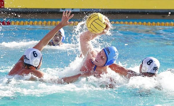 Corona del Mar High's Jack Trush, is surrounded and pressured by Northwood's JJ Meador (6) and Michael Garas (8) while scoring.