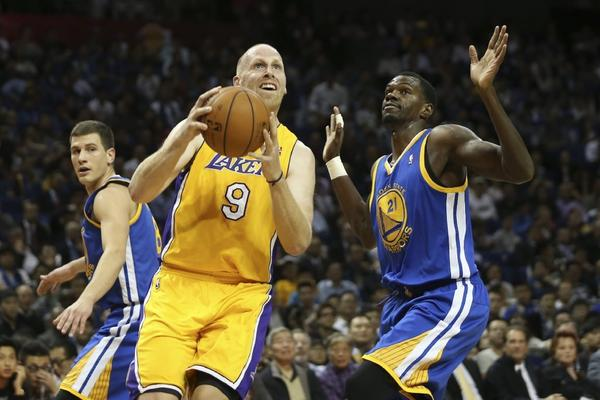 Chris Kaman of the Lakers goes to the basket against Dewayne Dedmon of the Golden State Warriors.