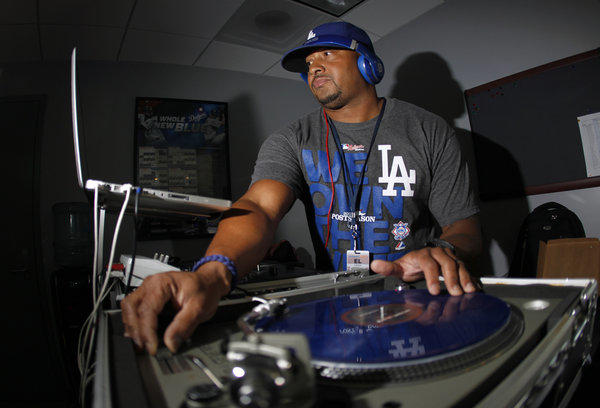 DJ Severe (Lanier Stewart) mixes music while fans arrive at Dodger Stadium as the Los Angeles Dodgers play the St. Louis Cardinals in Game 3 of the NLCS.