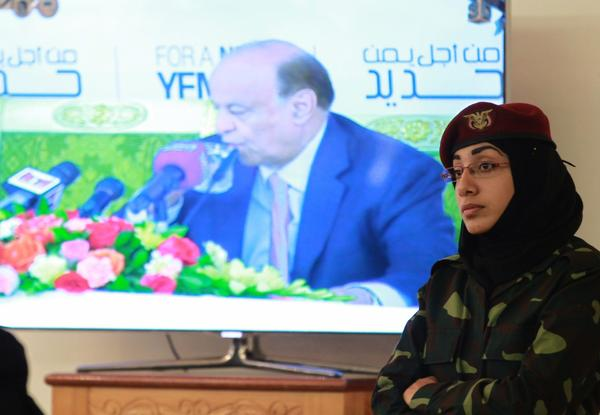 A Yemeni policewoman stands guard as an image of President Abdu Rabu Mansour Hadi is seen on a screen during a security conference in Sana.