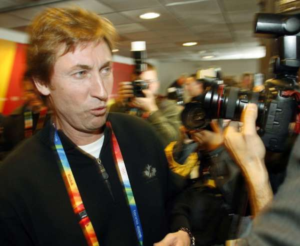 Wayne Gretzky makes his way through a crush of photographers after a news conference at the 2006 Winter Olympics in Turin.