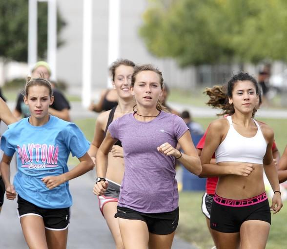 Kristen Heckert (center in purple tee), Plainfield South High School girl's cross country coach, sets the pace at team practice Sept. 17, 2013 in Plainfield. She was the fastest local woman runner in last year's Chicago Marathon and will also run this year.