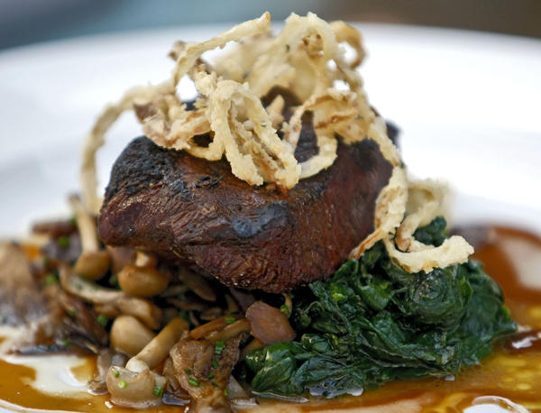 The Charbroiled flat-iron steak with wild mushrooms and organic spinach with garlic confit semi gloss at the Little Beast Restaurant in Eagle Rock on Thursday, Oct. 17, 2013.