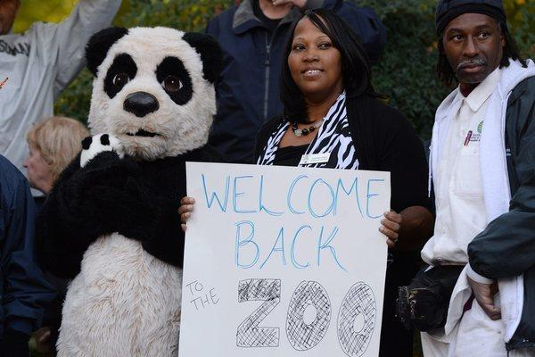 Employees at the Smithsonian National Zoological Park in Washington, D.C., welcome back visitors with signs and a panda costume. The zoo reopened to the public after the federal government shutdown ended.
