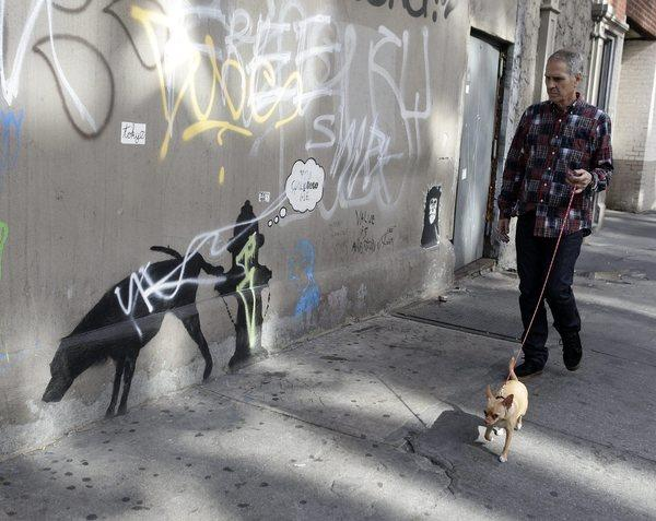A man walking his dog in New York checks out a work by Banksy this week that has been defaced.