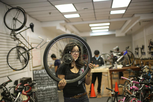 Bikes N' Roses participant Lizbeth Marin, 20, carries a wheel at the youth program's store on the 4700 block of North Kedzie Avenue Wednesdayo. The bicycle repair and education program run by the Albany Park Neighborhood Council is being cut back because it lost funding when the council was among a number of immigrant-rigthts coalition groups that backed a state gay marriage bill.