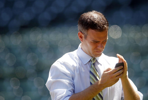 Cubs president Theo Epstein checks his phone before a July game.