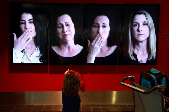 """Blow Me a Kiss"" by Eileen Cowin features video monitors with various people saying goodbye."