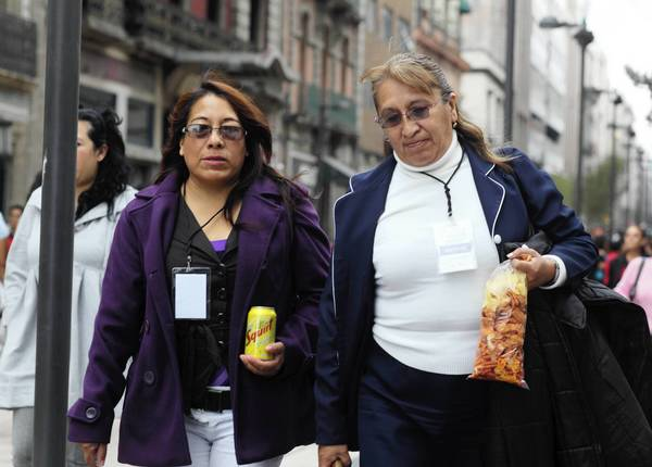Women in Mexico City carry a beverage and snacks. New legislation would tax high-calorie foods at 5% of the ticketed price and chewing gum at 16%. Soft drinks would go up in price about 8 cents per liter.