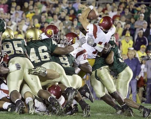 Trojans tailback Reggie Bush helps quarterback Matt Leinart get past Notre Dame defenders for a touchdown during a game at South Bend, Ind.