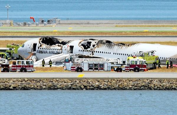 The wreckage of an Asiana Airlines jet rests on a runway at San Francisco International Airport after a July 6 crash landing. Officials say no charges will be filed against first responders, including the driver of a fire rig that ran over and killed a Chinese teen who was a passenger on the plane.