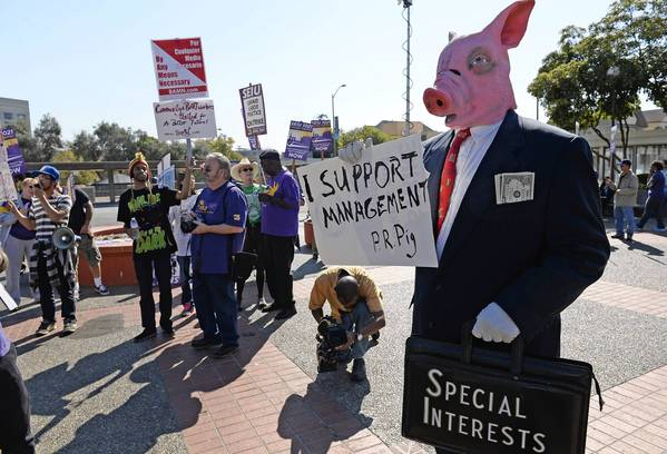 A protester in a pig mask mocks Bay Area Rapid Transit management at a rally with union members at the Lake Merritt BART Station in Oakland. A second strike by transit workers in four months produced traffic jams and frustration Friday, but officials predicted the worst was yet to come.