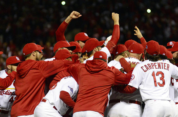 Members of the St. Louis Cardinals celebrate on the field after game six of the National League Championship Series baseball game against the Los Angeles Dodgers at Busch Stadium.