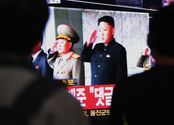 South Koreans watch a television broadcasting a video image of North Korean leader Kim Jong Un, right, at the Seoul Railway Station in South Korea.