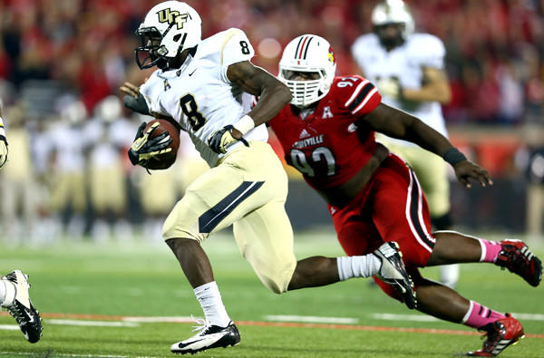 Central Florida running back Storm Johnson evades Louisville defensive tackle Brandon Dunn on a touchdown run during their game Friday night.