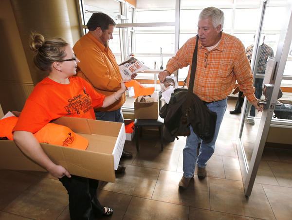 Holly DesCamps with Absolutely Aberdeen, left, and Casey Weismantel with the Aberdeen Convention and Visitors Bureau, center, greet John Olmstead of Cincinnati, Ohio, right, with gifts as he and other out-of-state hunters arrived Friday at Aberdeen Regional Airport.