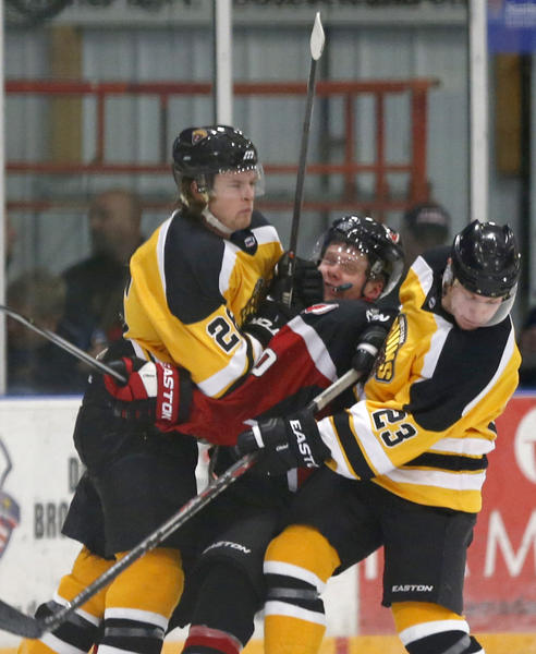 Tanner Okeson, of the Aberdeen Wings, center, gets sandwiched between Austin Bruins Trevor Boyd, left and Brian Bachnak, right, during the second period of Friday night's game at the Odde Ice Center. photo by john davis taken 10/18/2013