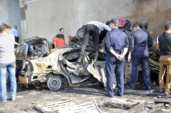 Egyptian police inspect the damage after a car bomb exploded outside a military intelligence base in the Suez Canal city of Ismailia.