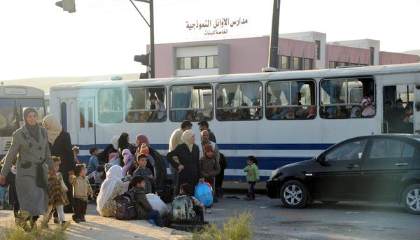 Syrians carry their belongings before getting into buses to take them from the Damascus suburb of Moadhamiya to Qudsayya, Syria, on Oct. 12.