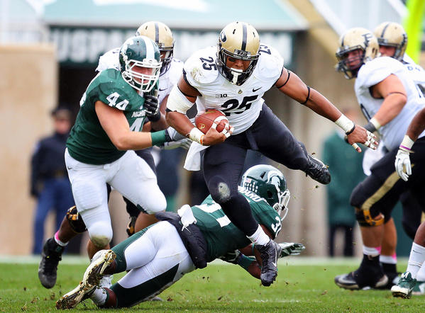 Purdue running back Brandon Cottom is up ended by Michigan State cornerback Darqueze Dennard (31).