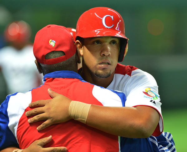Jose Abreu celebrates with a coach after his grand slam against China during the fifth inning of their first-round Pool A game in the World Baseball Classic tournament.