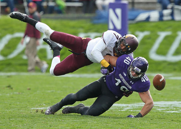 Northwestern's Dan Vitale is taken down during a reception attempt by Minnesota's Damarius Travis in the third quarter.