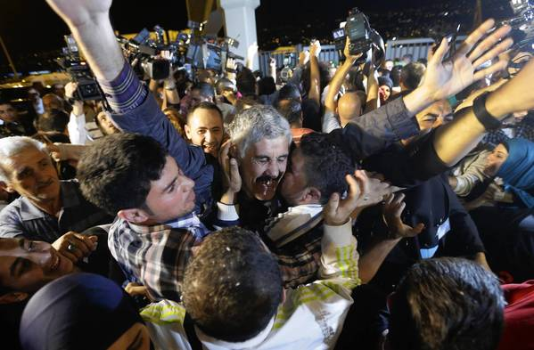 A Lebanese man freed by a rebel faction in Syria is mobbed by well-wishers at Rafik Hariri International Airport in Beirut.