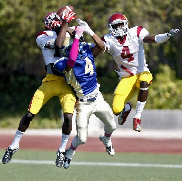 Glendale Community College's Dante Shipman, left, comes down with an interception in a 24-21 victory over West Los Angeles College.