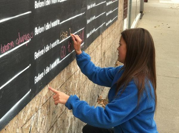 "Northern State University student Nicole Peterson of Gillette, Wyo., marks her spot on the ""Before I die ..."" board Friday on Main Street."