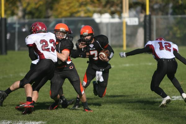 Oakes quarterback Bryce Meehl (7) carries the ball while teammate Erik Loepp gets a block on Walker Carr (23) of Carrington. Connor Wendel (12) is at right.