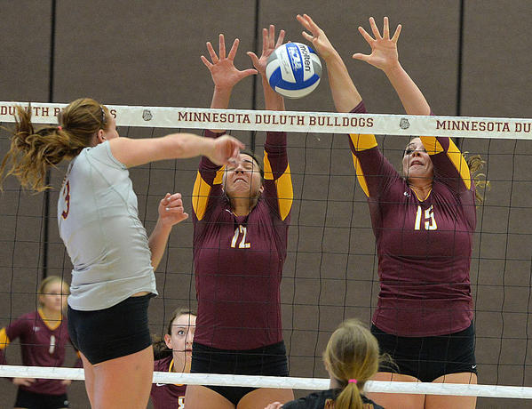 Northern States Jussy Tuscherer, left, goes up for a kill against Minnesota-Duluths Maddy Siroin (12) and Sydnie Mauch (15) on Saturday in Duluth, Minn. The Wolves upset the No. 2 ranked Bulldogs.