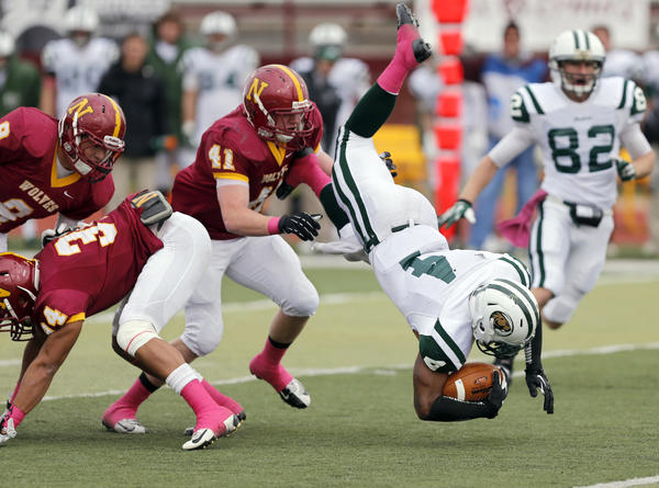 Bemidji State's Avery Walker (4) is tripped up by Northern State University's Logan Dosch (34) as Ryan Weybrecht (9) and Michael Alberts (41) help out on the play in the first half of Saturday's game at Swisher Field. In the background for Bemidji is Vince Dinkel (82). photo by john davis taken 10/19/2013