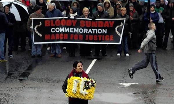 Linda Nash, whose brother William Nash was one of 14 killed, carries a floral tribute at a memorial service to mark the 40th anniversary of Bloody Sunday in Londonderry.
