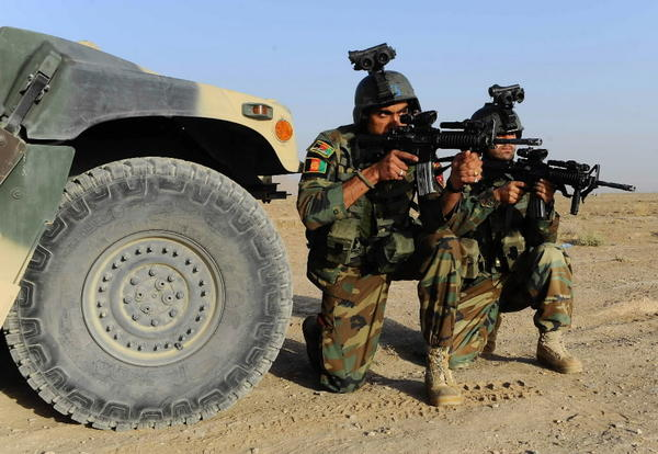 Afghanistan National Army (ANA) special forces point their weapons during an anti-Taliban commander in the Gozara district of Herat province on September 28, 2013.