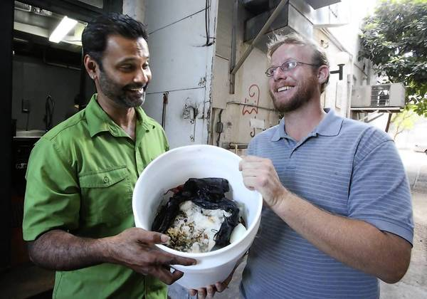 Ben Walter from Hermitage Farms picks the weekly food waste from Cress Restaurant in DeLand. Chef and owner Hari Pulapaka, left, gives a bucket of uneaten food stuff to Walter. This is the equivalent of about 50 pounds of animal feed for his farm. The grassroots program aims to link merchants and farmers to create a sustainable system that recyles and re-purposes the thousands of pounds of food weekly.