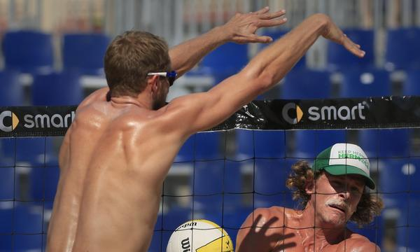 Theodore Brunner, left, blocks a shot during match play at the AVP Championships in Huntington Beach on Friday.
