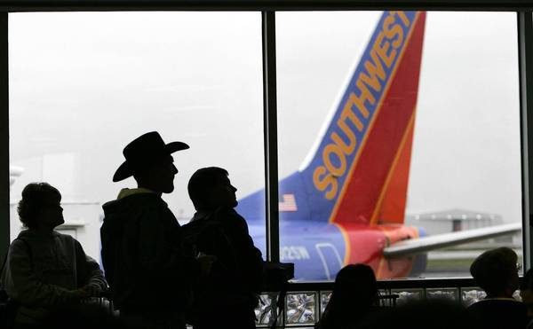 Southwest Airlines is expected to add many new nonstops from Texas' Love Field next fall, putting the low-cost airline in direct competition with American Airlines, based at nearby Dallas-Fort Worth International Airport. Above, passengers wait to board a Southwest flight at Love Field in November 2004.